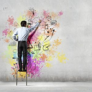 Back view of businessman drawing colorful business ideas on wall | Quelle: iStock
